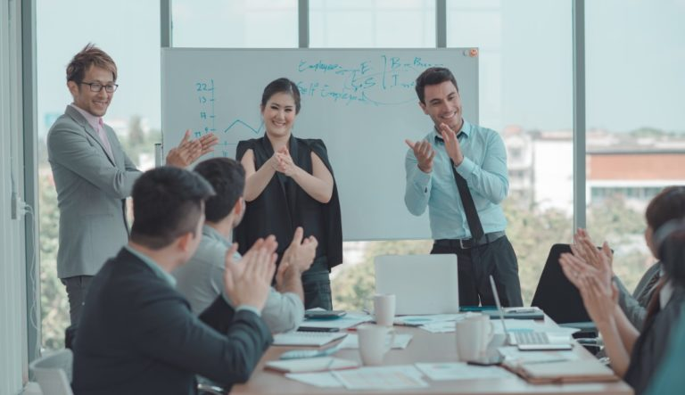 People clapping hands at a business meeting
