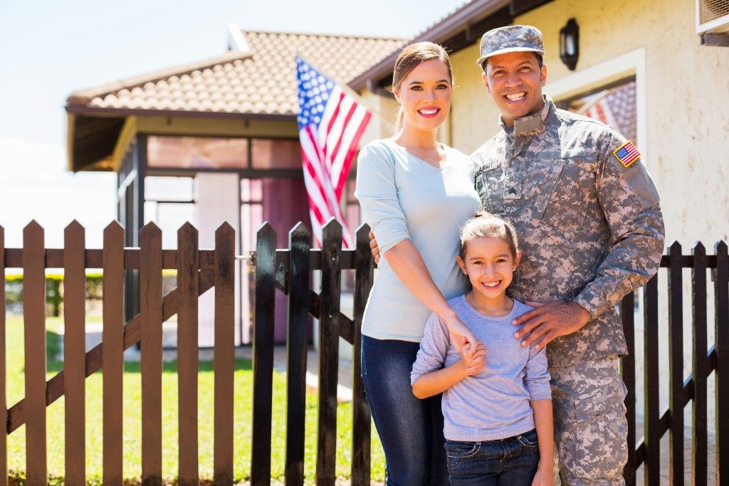 american soldier with family outside their home