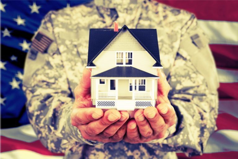 an armed force member holding a miniature house