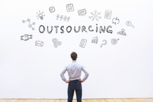 businessman looking at word outsourcing