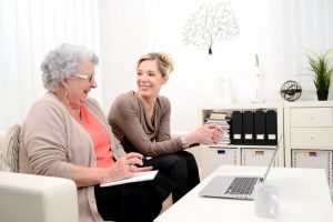 woman teaching elderly how to use a laptop