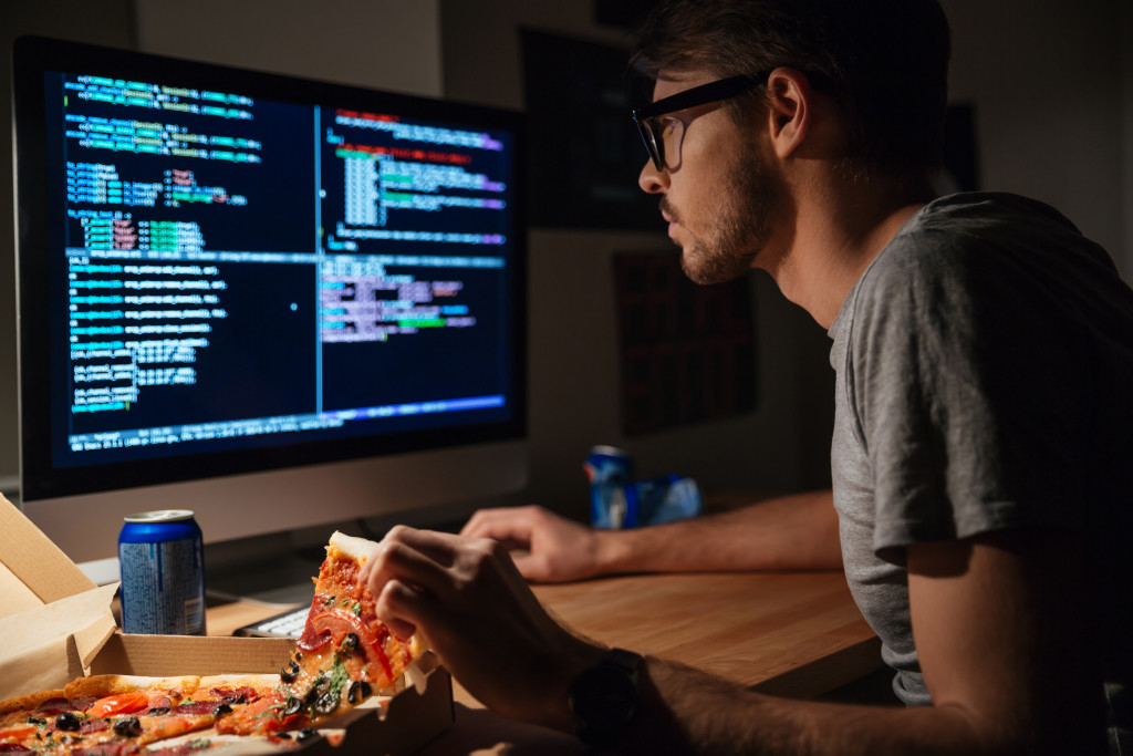 man working on computer with pizza
