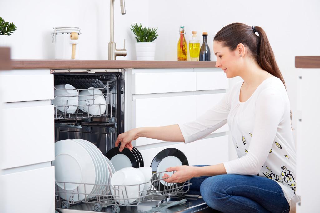 woman loading up the dishwasher